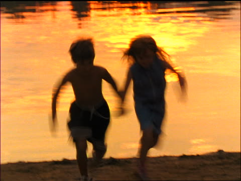 vidéos et rushes de slow motion laughing boy + girl holding hands + running towards camera at sunset / north stanhope, nj - couple d'adolescents