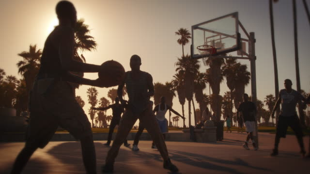 slow motion lens flare shot of basketball game near venice beach, california - basketball ball stock videos & royalty-free footage