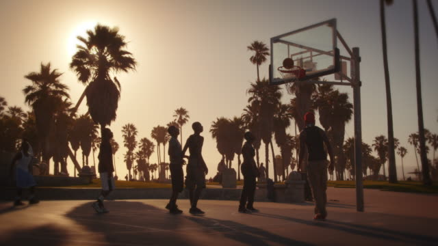Slow motion lens flare shot of men playing basketball near Venice Beach, California