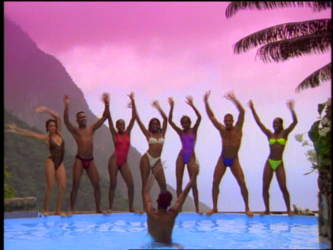 slow motion line of people in swimsuits dance by pool + jump in - medium group of people stock videos & royalty-free footage