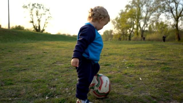 vídeos de stock, filmes e b-roll de rapaz pequeno do movimento lento que joga o futebol - termo esportivo