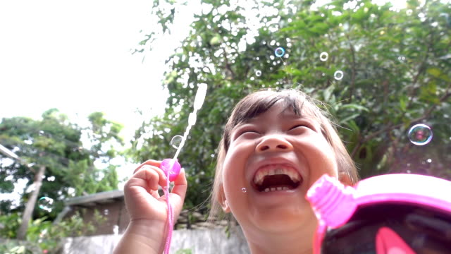 slow motion little girl blowing bubbles - sundress stock videos & royalty-free footage