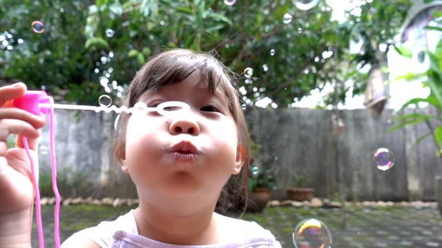 Slow motion Little Girl Blowing Bubbles