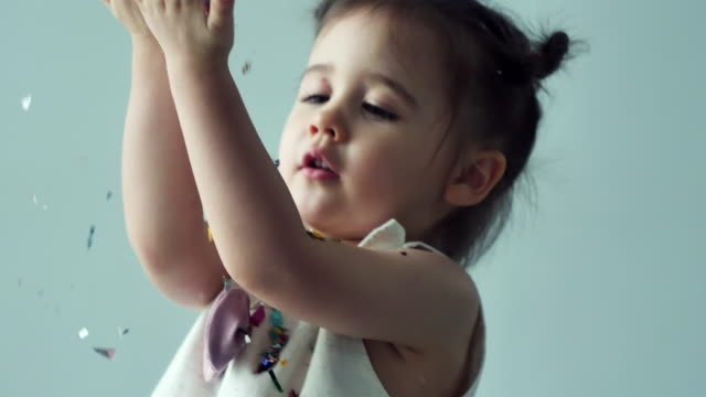slow motion : little girl playing colorful confetti - 2 3 years stock videos & royalty-free footage