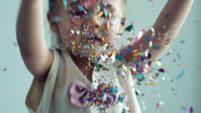 slow motion : little girl throwing colorful confetti - braided hair stock videos & royalty-free footage