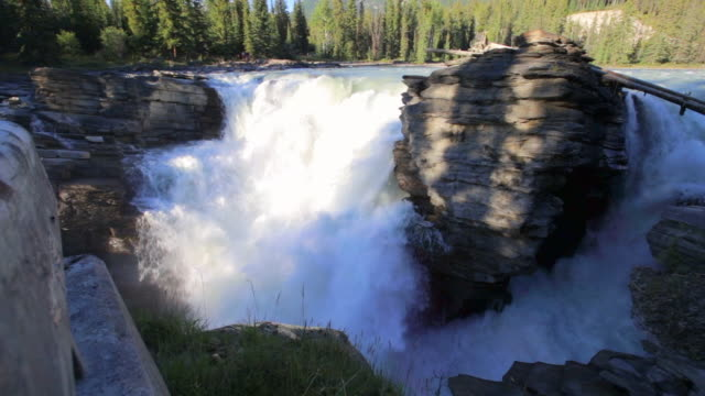 slow motion lockdown shot of beautiful cascade through rocks at famous national park - jasper national park, canada - jasper national park stock videos & royalty-free footage