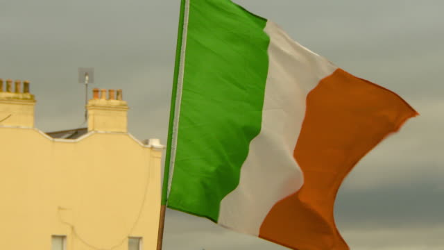 slow motion lockdown shot of irish flag waving in city against sky - dublin, ireland - quarantena video stock e b–roll