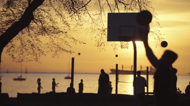 vídeos y material grabado en eventos de stock de slow motion lockdown shot of people playing basketball by water during sunset - crepúsculo