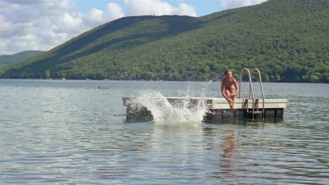 Slow motion long shot boy and girl doing cannonballs off raft into lake / swimming / Canandaigua Lake, New York