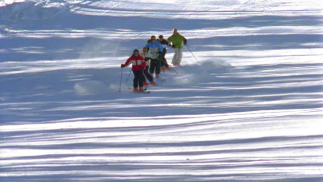 vidéos et rushes de slow motion long shot five people skiing in line towards camera on mountain slope - mountain range