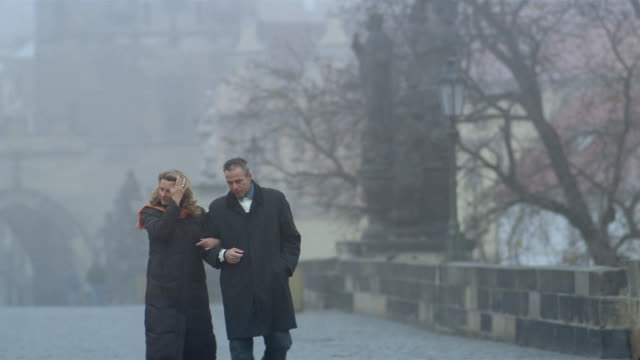 Slow motion long shot man and woman walking on Charles Bridge on foggy day / Prague