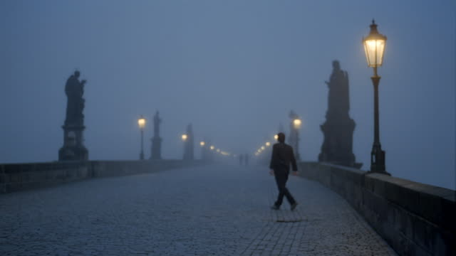 Slow motion long shot man walking alone on Charles Bridge at night / Prague