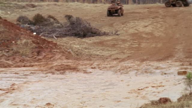 slow motion long shot pan three teenage boys riding down hill on 4-wheeled atvs and splashing into large muddy puddle - quadbike stock videos & royalty-free footage