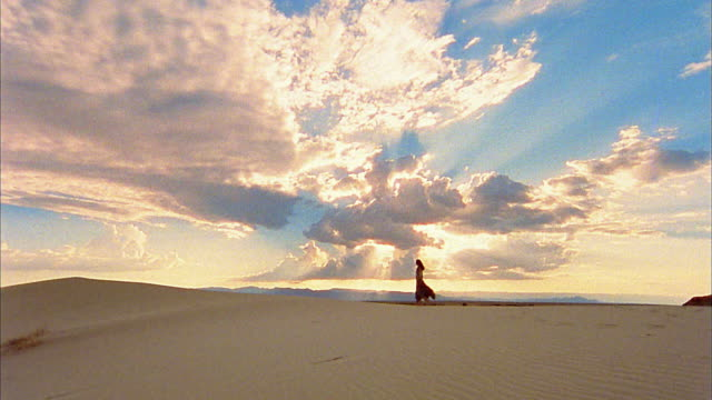 Slow motion long shot silhouetted woman walking on beach