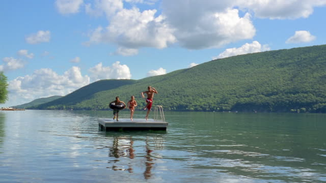Slow motion long shot three children jumping off raft into lake / Canandaigua Lake, New York