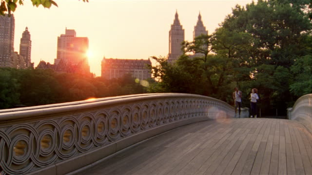 slow motion long shot young man and woman jogging across bow bridge in central park at sunset / new york city - central park manhattan stock videos & royalty-free footage