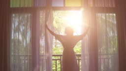 Slow motion. Lovely woman opening colorful curtains and meeting sunrise. View from balcony to jungle.