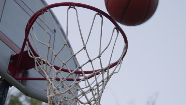 slow motion low angle artistic moving handheld shot of a tall outdoor basketball sports hoop net goal basket under a clear gray sky on a summer evening around sunset golden hour - basket stock videos & royalty-free footage