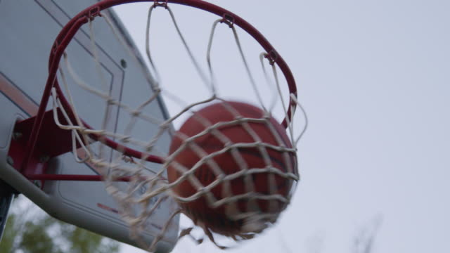 vidéos et rushes de slow motion low angle artistic moving handheld shot of a tall outdoor basketball sports hoop net goal basket under a clear gray sky on a summer evening around sunset golden hour - panier