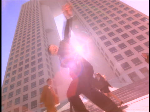 slow motion low angle asian businessman spinning with briefcase / businesspeople + office building in background / mexico - 1998 stock-videos und b-roll-filmmaterial