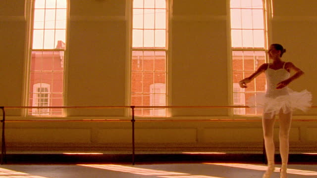 vídeos y material grabado en eventos de stock de orange slow motion low angle ballerina spinning past three arched windows - malla de gimnasia