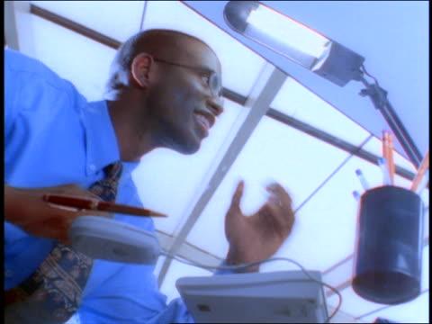 vídeos de stock, filmes e b-roll de blue slow motion low angle black businessman sitting at desk looking at computer + smiling - vestuário de trabalho formal