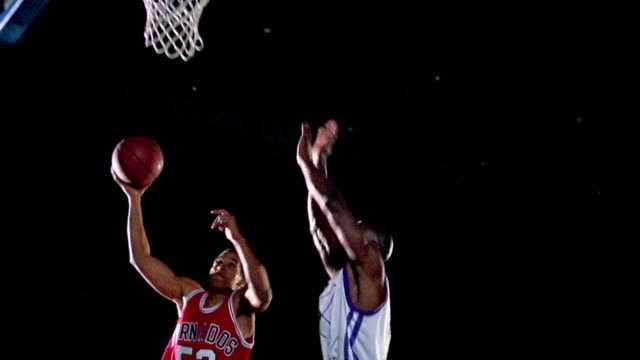 slow motion low angle black man in red uniform dunking basketball as black man in white uniform tries to block - basketball stock videos and b-roll footage