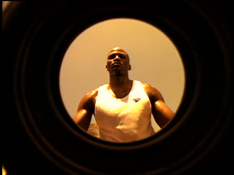 sepia slow motion low angle black man in tank top lifting old tire in junkyard + holding it with 1 hand - getönt stock-videos und b-roll-filmmaterial