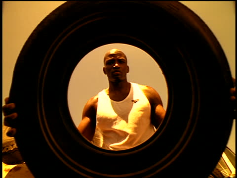 sepia slow motion low angle black man in tank top lifting old tire in junkyard - manipolazione di colore video stock e b–roll
