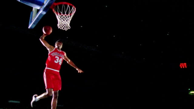 slow motion low angle Black man in uniform dunking basketball walking toward camera with attitude