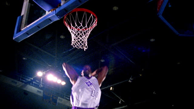slow motion low angle Black man in white uniform dunking basketball + hanging on rim of hoop in arena