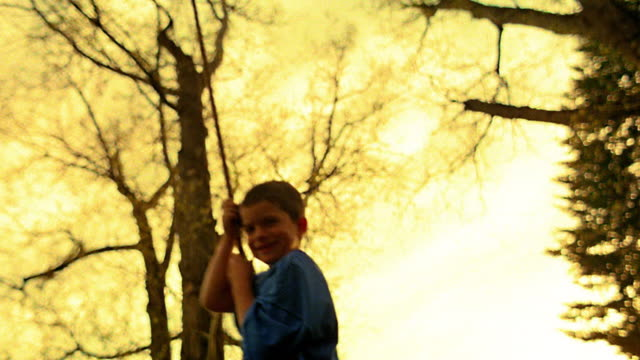 vídeos de stock e filmes b-roll de yellow slow motion low angle boy swinging on rope tree swing + smiling / trees in background / montana - super exposto
