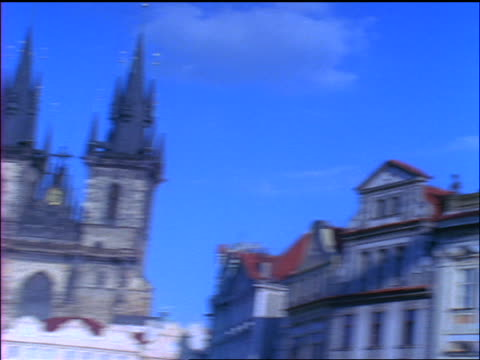 blue slow motion low angle pan buildings to tyn church in old town square / prague, czech republic - altstädter ring stock-videos und b-roll-filmmaterial