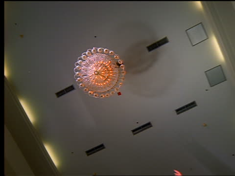 stockvideo's en b-roll-footage met slow motion low angle businessman holding jacket flying above camera underneath chandelier in large room - mid volwassen mannen