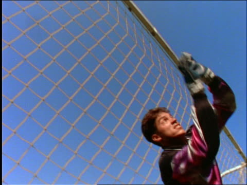 vídeos de stock e filmes b-roll de slow motion low angle close up goalie saving ball in soccer game - lugar genérico
