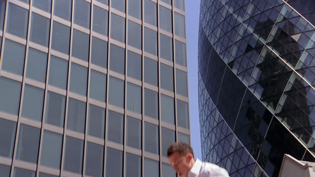 vidéos et rushes de slow motion low angle close up man bouncing in air against building in background / flipping in air - agilité entreprise
