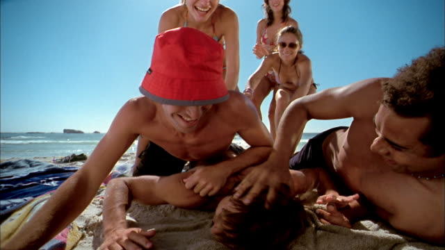 stockvideo's en b-roll-footage met slow motion low angle close up men and women running on beach + jumping on top of man's back - volwassen