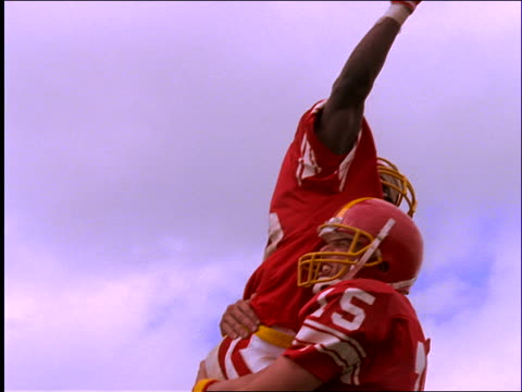 slow motion low angle close up of 2 football players jumping and hugging