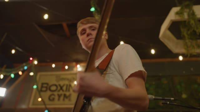 stockvideo's en b-roll-footage met slow motion low angle close up of guitarist practicing bass guitar in nightclub / provo, utah, united states - provo