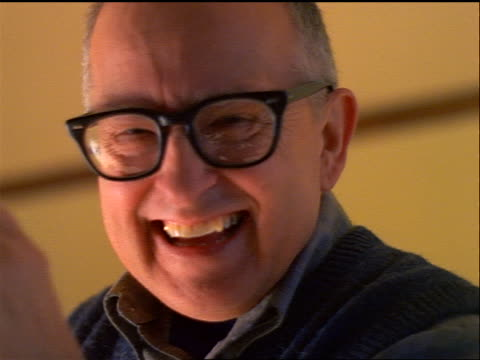 slow motion low angle close up PORTRAIT senior man with eyeglasses laughing + putting hand to mouth indoors