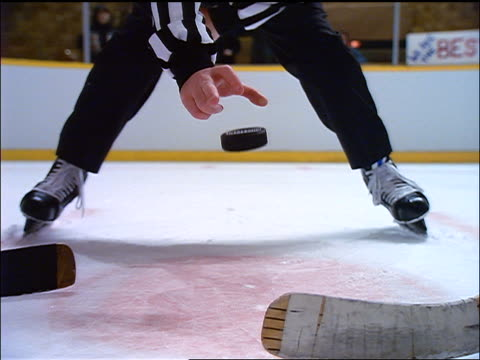 slow motion low angle close up referee dropping puck in ice hockey game face off