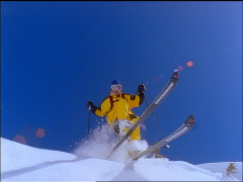 slow motion low angle close up pan skier jumping over camera / europe - skiwear stock videos & royalty-free footage