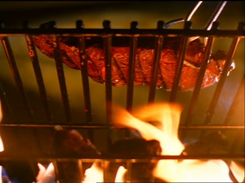 slow motion low angle close up steak cooking over open flame being flipped by tongs - bordsyteinspelning bildbanksvideor och videomaterial från bakom kulisserna