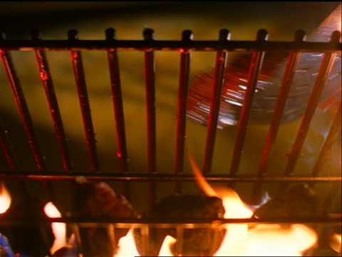 slow motion low angle close up steak cooking over open flame being flipped by metal spatula - steak stock videos & royalty-free footage