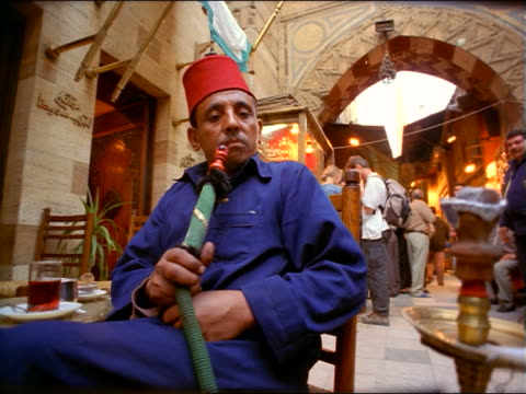 slow motion low angle dolly shot seated egyptian man wearing fez smoking water pipe in bazaar / khan al-khalili / cairo - hat stock videos and b-roll footage