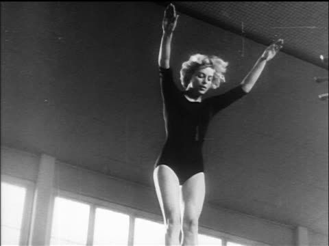 stockvideo's en b-roll-footage met b/w 1960 slow motion low angle female gymnast on trampoline in championship / germany / newsreel - trampoline