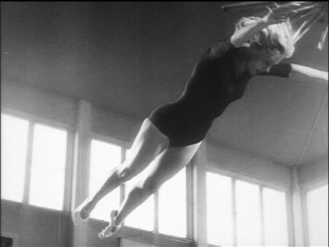slow motion low angle female gymnast on trampoline in championship / germany / newsreel - 1960 stock-videos und b-roll-filmmaterial