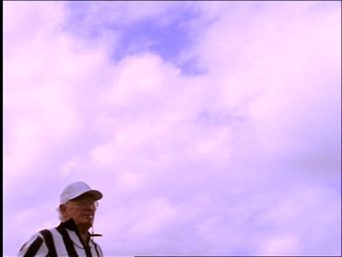 slow motion low angle footbal referee blows whistle and throws flag - trillerpfeife stock-videos und b-roll-filmmaterial
