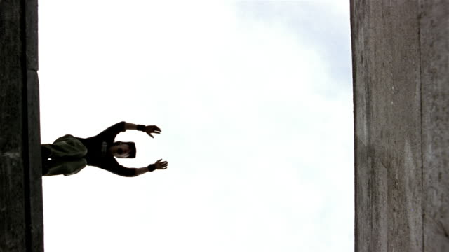 Slow motion low angle freerunner jumping from one roof to another