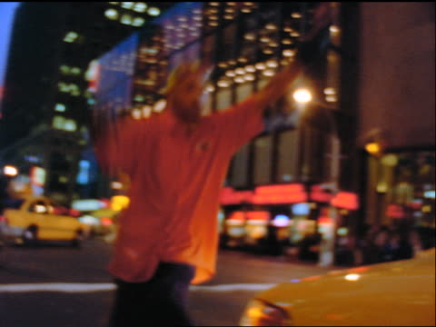 slow motion low angle pan gen x man with yellow hair skating past camera on street in times square at night - x世代点の映像素材/bロール